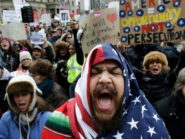 Izzy Berdan, of Boston, center, wears an American flags as he chants slogans with other demonstrators during a rally against President Trump's order that restricts travel to the U.S., Sunday, Jan. 29, 2017, in Boston. Trump signed an executive order Friday, Jan. 27, 2017 that bans legal U.S. residents and visa-holders from seven Muslim-majority nations from entering the U.S. for 90 days and puts an indefinite hold on a program resettling Syrian refugees. (AP Photo/Steven Senne)